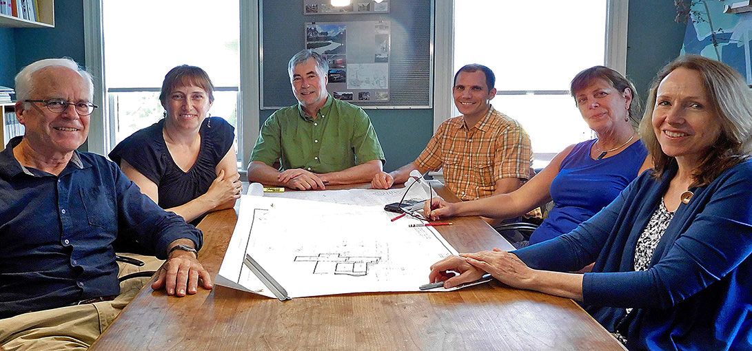 Color photo of Whipple Callender Architects staff sitting around conference room table